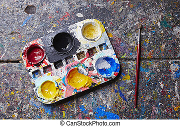 Palette with paintbrush on the desk in workshop
