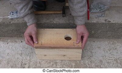 hammering nail in bird house - hammering nail in new wooden...