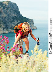 woman hiking - young blonde woman hiking and smiling. Copy...