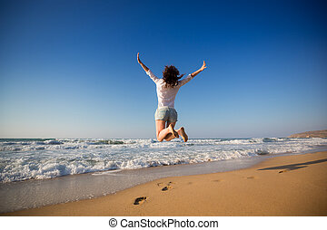 Happy woman jumping at the beach. Summer vacation concept