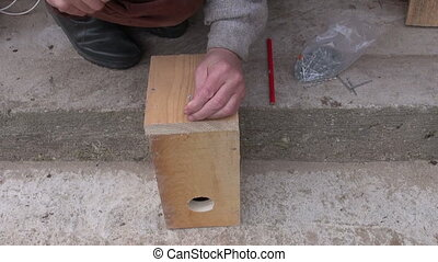 hammering nail in wooden bird house
