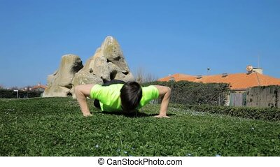 Young athlete doing push ups - Forward dolly shot young...