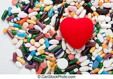 Red heart on pills - Pile of colorful pills with red heart