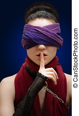 Blindfolded girl finger over lips Blue Background
