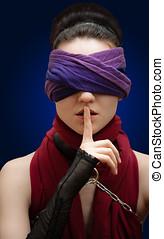Blindfolded girl finger over lips Blue Background