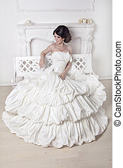 Beautiful bride woman sitting on luxuriant wedding dress...