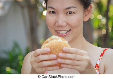 Woman eating a hamburger - Asian girl eating a hamburger in...