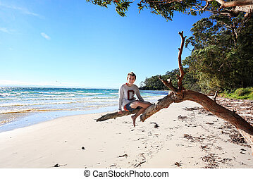 Teen boy sitting on a gum tree outstretched branch enjoying a vacation on a glorious day at the beach in NSW Australia