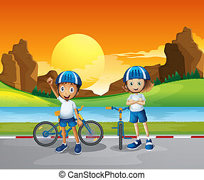 Two kids with their bikes standing at the road near the...