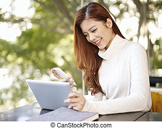 young woman working in coffee shop - asian young woman...