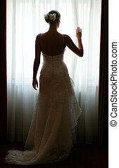Bride silhouetted by window - Rear view of young bride stood...