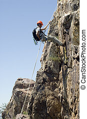 Climber rappelling making a vertical mountain wall
