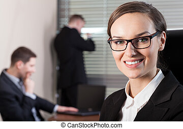 Businesswoman and workers in the office, horizontal