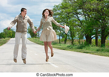 happy couple jumping on rural road