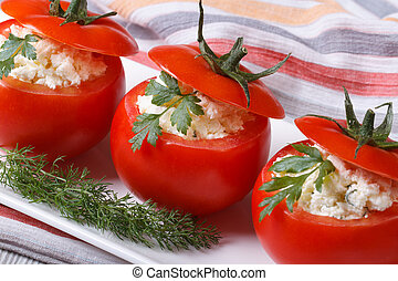 Fresh red tomatoes filled with soft cheese and herbs close...