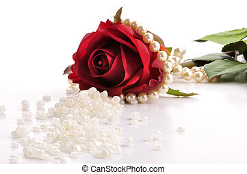red rose and pearls - red rose on a white surface with...