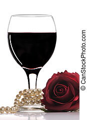 romantic atmosphere - glass of red wine with pearls and a...