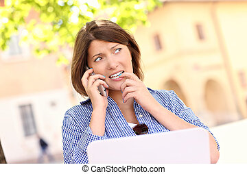 Worried woman with laptop in the park - A picture of a...
