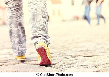 Female legs on paving blocks