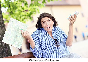 Lost woman with map and cellphone