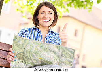Young traveler - Young woman with map sitting on a bench