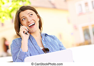 Young woman on the phone with laptop
