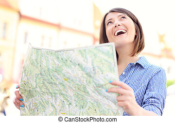 Happy tourist - Happy young tourist with map in the town