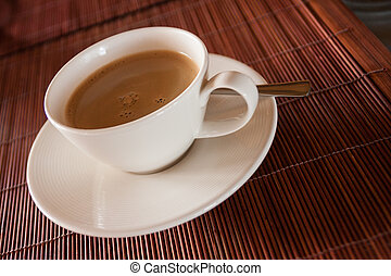 Steaming hot cup of black coffee on wooden tablemat