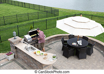 Man cooking meat on a gas BBQ - High angle view of a man...