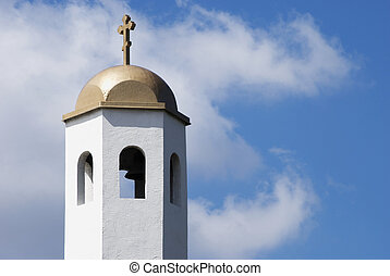 Church Bell Tower with Cross and dome against a blue sky