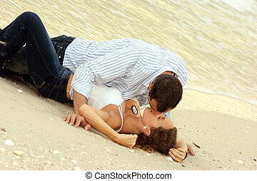 young attractive couple making love on the beach - Beautiful...
