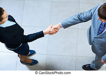 Business woman and businessman shaking hands, reach...