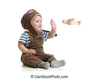child boy playing with wooden plane
