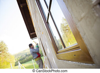 Man insulating windows - Man applying foam sealant with...