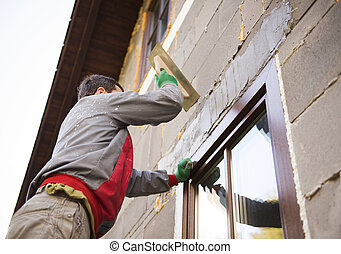 Man plastering - Plasterer spreading out plaster with trowel...