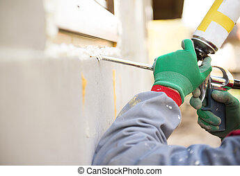 Man insulating windows - Man applying foam sealant with...