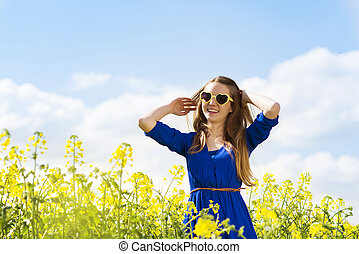 Girl in colza field - Happy young girl in blue dres nad...