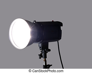 Studio monolight flash unit firing against gray background -...