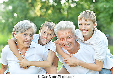 Kids with grandparents - Older couple standing with their...