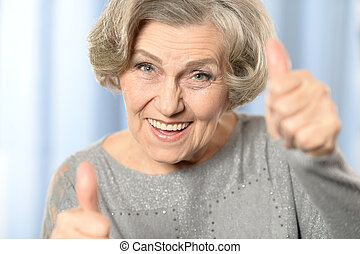 Happy old woman - Beautiful old woman showing thumbs up on a...