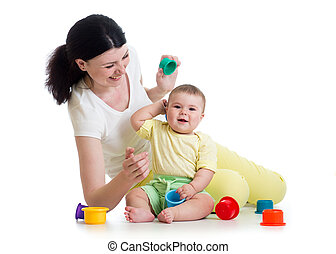 kid girl and mother playing together with cup toys
