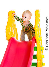 toddler boy playing on the slide