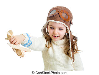 smiling child dressed pilot and playing with wooden airplane toy