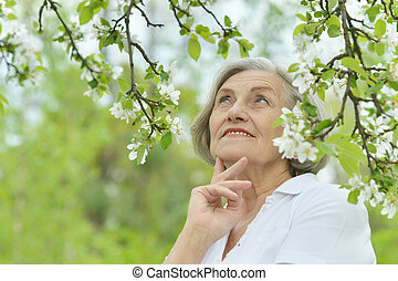 Pensive elderly woman walking in the summer nature