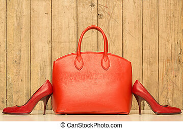 Woman accessories on wood background, red handbag and...
