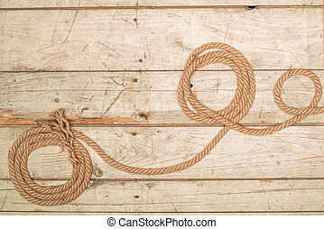 Ropes on a wooden background - old texture of wooden boards...