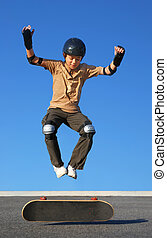 Boy Jumping High from Skateboard - Boy with protective gear...