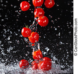 Cherry tomato in water splash on black background - Studio...