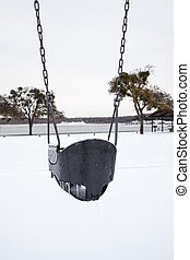 winter swing - Ice covered swing in a park with snow covered...