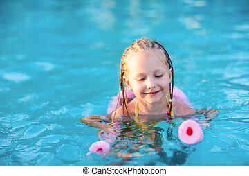 Little girl in a swimming pool - Adorable little girl...